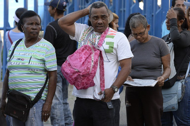 People queue outside Venezuela's Central Bank (BCV) in Caracas in an attempt to change 100 Bolivar notes, on December 16, 2016. Venezuelans lined up to deposit 100-unit banknotes before they turned worthless, but replacement bills had yet to arrive, increasing the cash chaos in the country with the world's highest inflation. Venezuelans are stuck in currency limbo after President Nicolas Maduro ordered the 100-bolivar note -- the largest denomination, currently worth about three US cents -- removed from circulation in 72 hours. / AFP PHOTO / FEDERICO PARRA