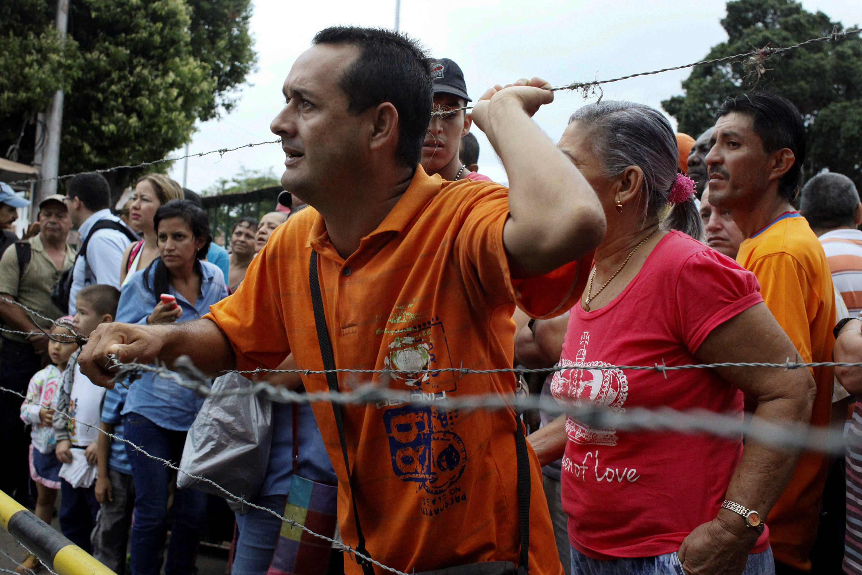 People stand next to barbed wire fences as they try to cross the border to Colombia over the Francisco de Paula Santander international bridge in Urena