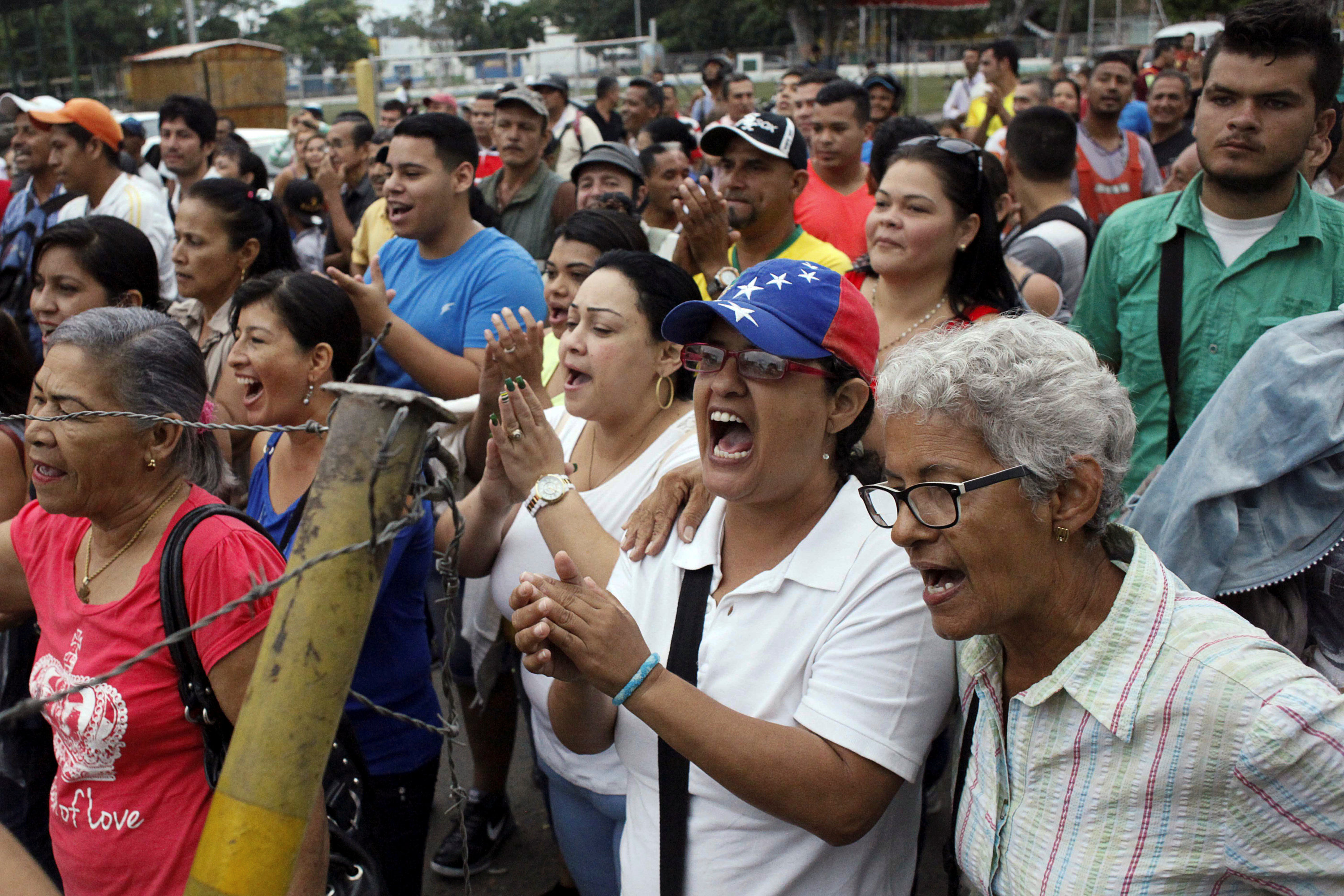 People shout slogans as they wait to try to cross the border to Colombia over the Francisco de Paula Santander international bridge in Urena