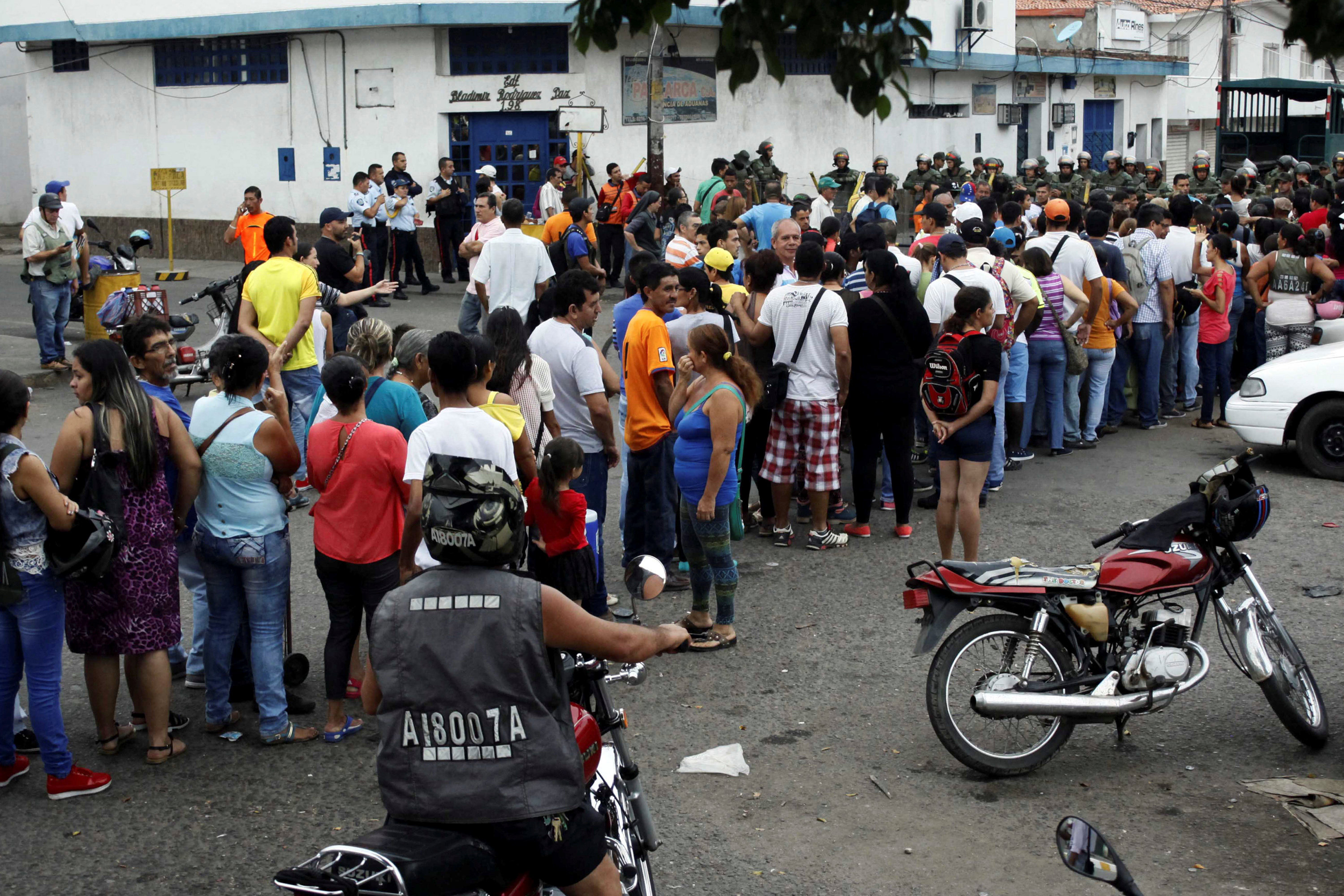 People make a line in front of Venezuelan National Guards as they wait to try to cross the border to Colombia over the Francisco de Paula Santander international bridge in Urena