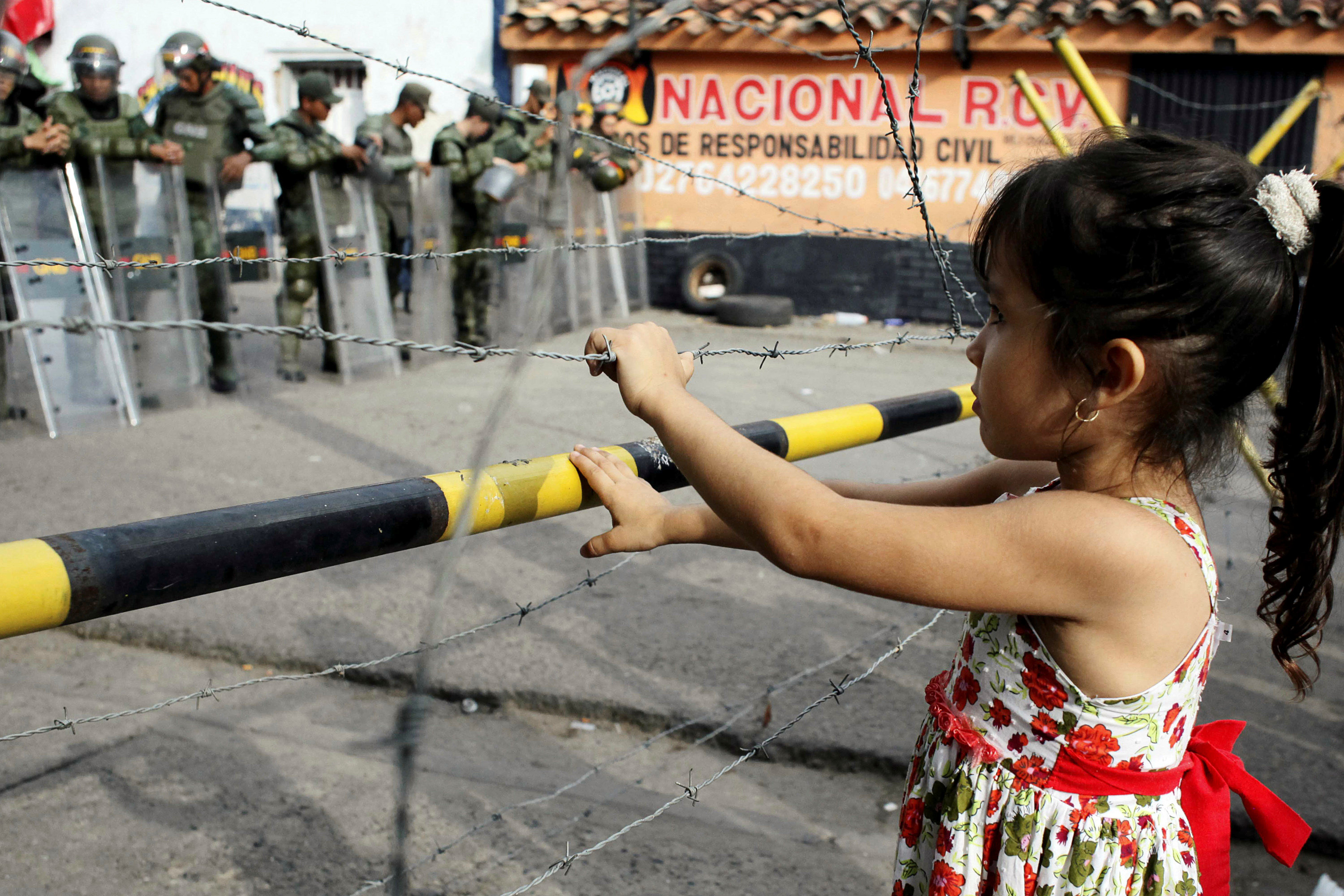 A girl stands next to a barbed wire fence as she waits to try to cross the border to Colombia over the Francisco de Paula Santander international bridge in Urena, Venezuela