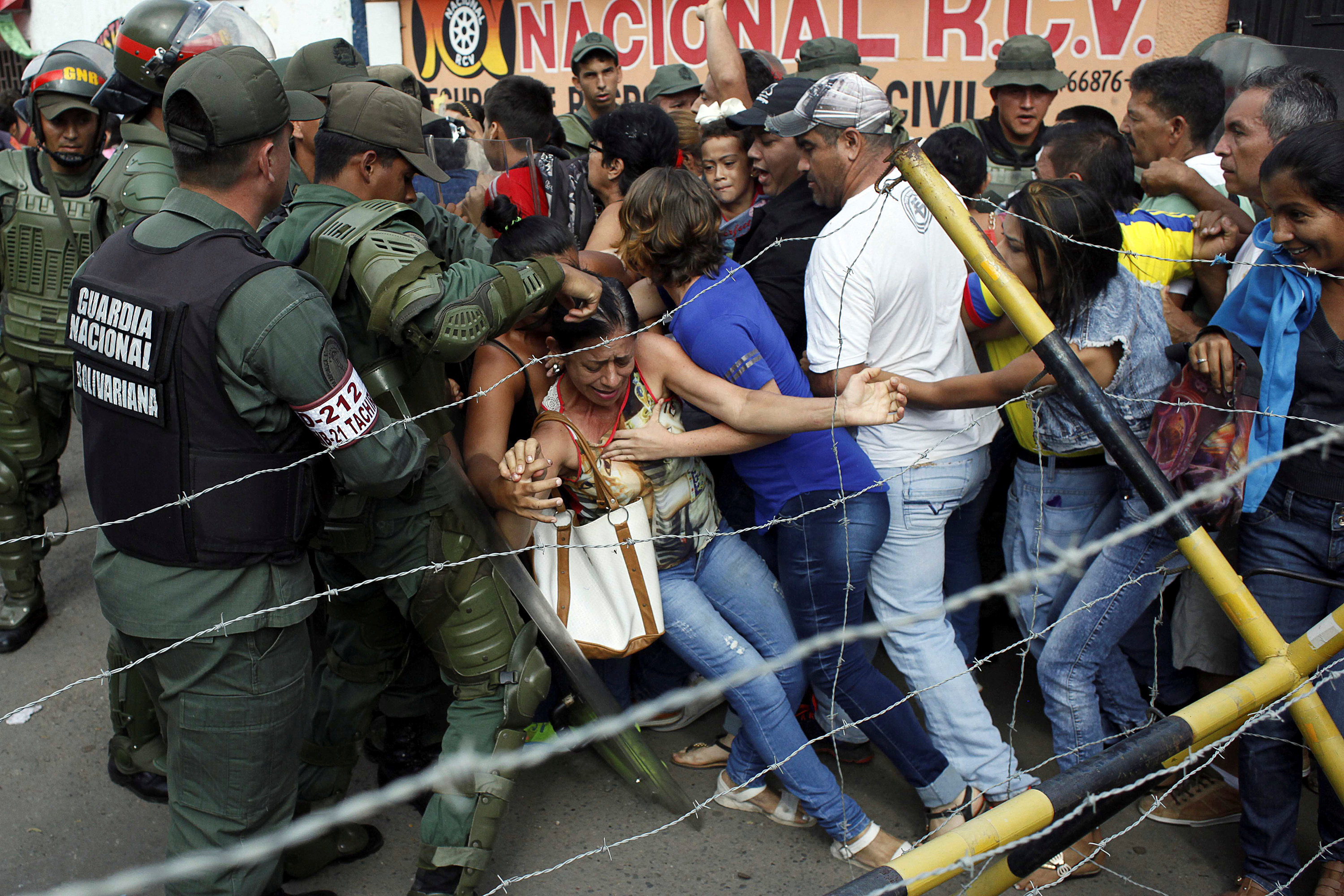 People clash with Venezuelan National Guards as they try to cross the border to Colombia over the Francisco de Paula Santander international bridge in Urena