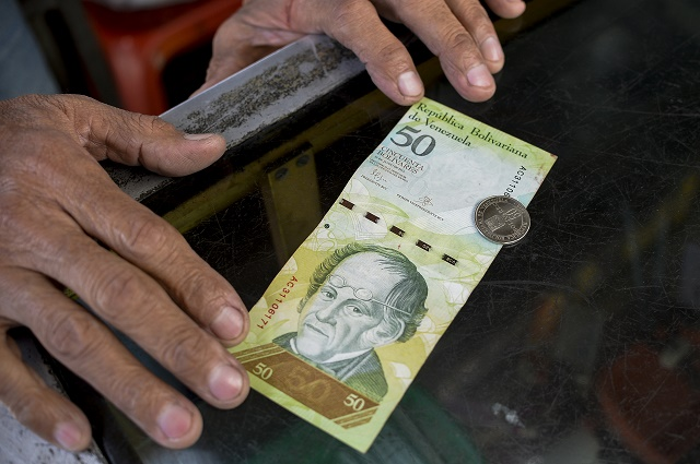 A man compares a new 50-Bolivar-coin with a Bolivar-note of the same denomination at a kiosk in Caracas on December 28, 2016. Venezuela took delivery on December 27 of its third load of new, bigger denomination banknotes, its central bank said, but there was no sign of them in circulation yet despite official promises and mounting public anxiety. Maduro's announcement that the 100-bolivar notes would suddenly no longer be legal tender provoked long lines of people trying to change them, and looting and rioting in some areas, resulting in four deaths. / AFP PHOTO / FEDERICO PARRA