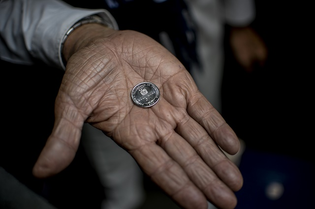 A man holds a new 50-Bolivar-coin in downtown Caracas on December 28, 2016. Venezuela took delivery on December 27 of its third load of new, bigger denomination banknotes, its central bank said, but there was no sign of them in circulation yet despite official promises and mounting public anxiety. Maduro's announcement that the 100-bolivar notes would suddenly no longer be legal tender provoked long lines of people trying to change them, and looting and rioting in some areas, resulting in four deaths. / AFP PHOTO / FEDERICO PARRA