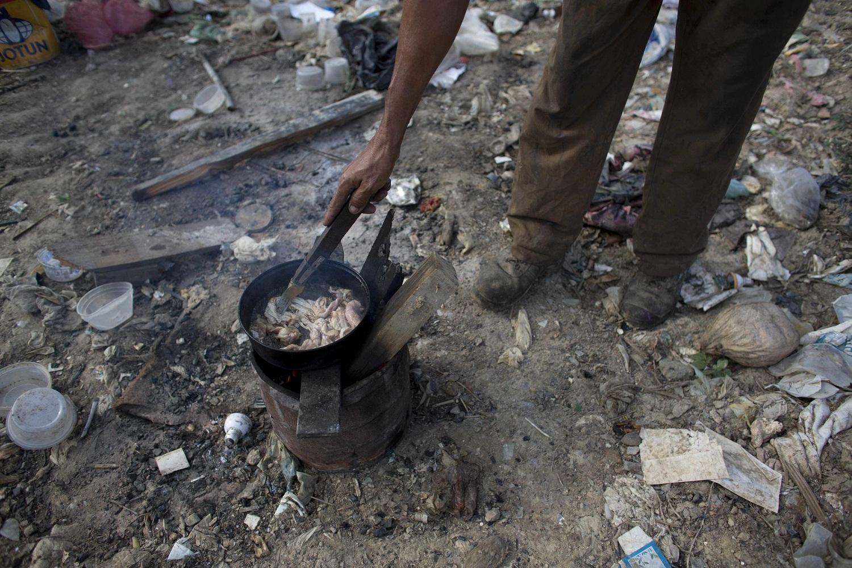 En esta imagen del 1 de noviembre de 2016, un hombre cocina piel de pollo que encontró en un basurero de Puerto Cabello, Venezuela la ciudad portuaria  a la que llega la mayoría de la comida importada del país. Cuando la comida importada se estropea en puerto, el ejército intenta librarse de ella con discreción enterrándola en vertederos como este. Los vecinos dijeron que han podido recuperar avena, pipas de girasol y alimento para cerdos tirado por el ejército este año. (AP Foto/Ariana Cubillos)