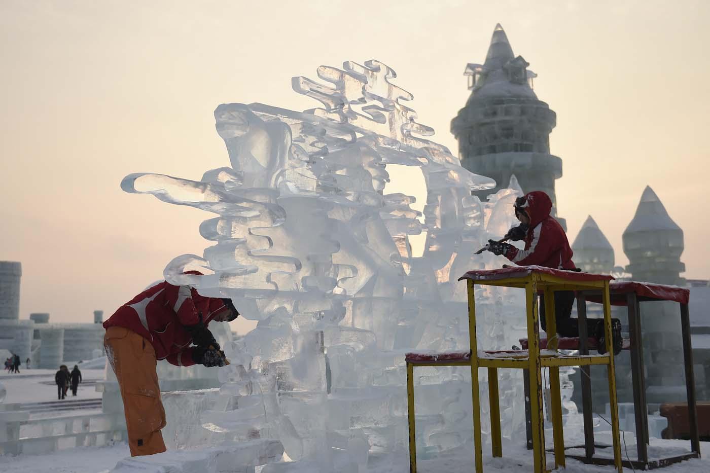 En esta imagen, tomada el 3 de enero de 2017 y distribuida por la agencia china de noticias Xinhua, dos participantes tallan una escultura de hielo durante el concurso de esculturas del  Festival Internacional de Hielo y Nueve de Harbin, en la provincia de Heilongjiang, en el noreste de China. La ciudad de Harbin, en el gélido noreste de China, da los últimos retoques previos a la apertura de uno de los festivales de hielo más grandes del mundo, que el año pasado atrajo a más de un millón de visitantes. (Wang Jianwei/Xinhua via AP)