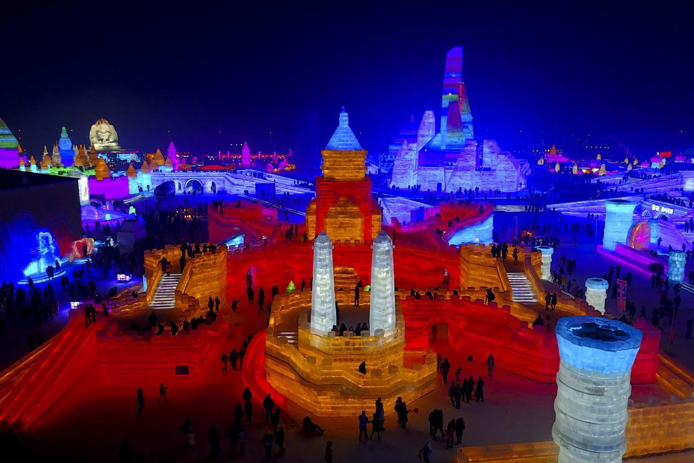 En esta imagen, tomada el 31 de diciembre de 2016, visitantes pasean por una escultura con forma de castillo fabricada con bloques de hielo durante el Festival Internacional de Hielo y Nueve de Harbin, en la provincia de Heilongjiang, en el noreste de China. (Chinatopix via AP)