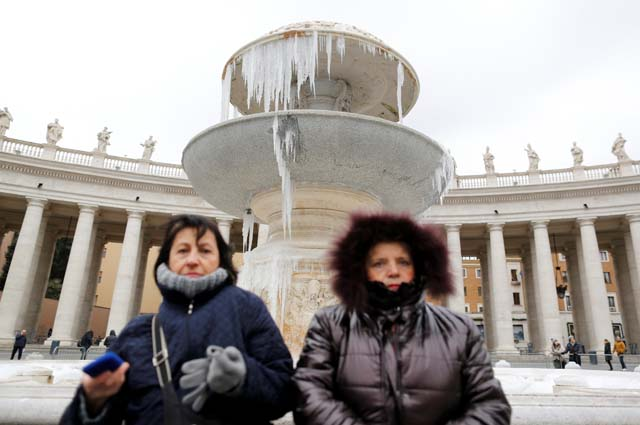 People stand in front of a frozen fountain on a cold winter day in Saint Peter's square at the Vatican January 8, 2017. REUTERS/Tony Gentile