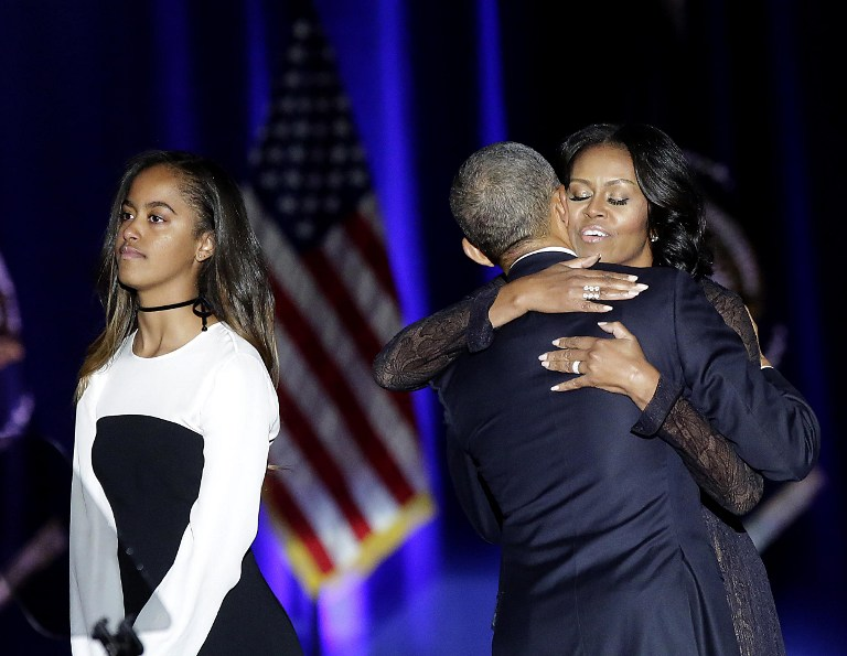 US First Lady Michelle Obama (R) hugs US President Barack Obama as daughter Malia looks on after the President delivered his farewell address in Chicago, Illinois on January 10, 2017. Barack Obama closes the book on his presidency, with a farewell speech in Chicago that will try to lift supporters shaken by Donald Trump's shock election. / AFP PHOTO / Joshua LOTT