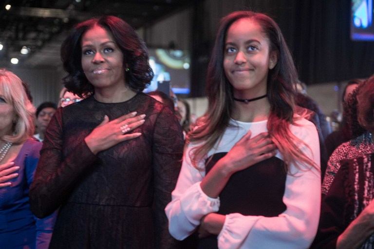 US First Lady Michelle Obama (L) and daughter Malia listen to the national anthem before President Barack Obama delivered his farewell address in Chicago, Illinois on January 10, 2017. Barack Obama closes the book on his presidency, with a farewell speech in Chicago that will try to lift supporters shaken by Donald Trump's shock election. / AFP PHOTO / NICHOLAS KAMM