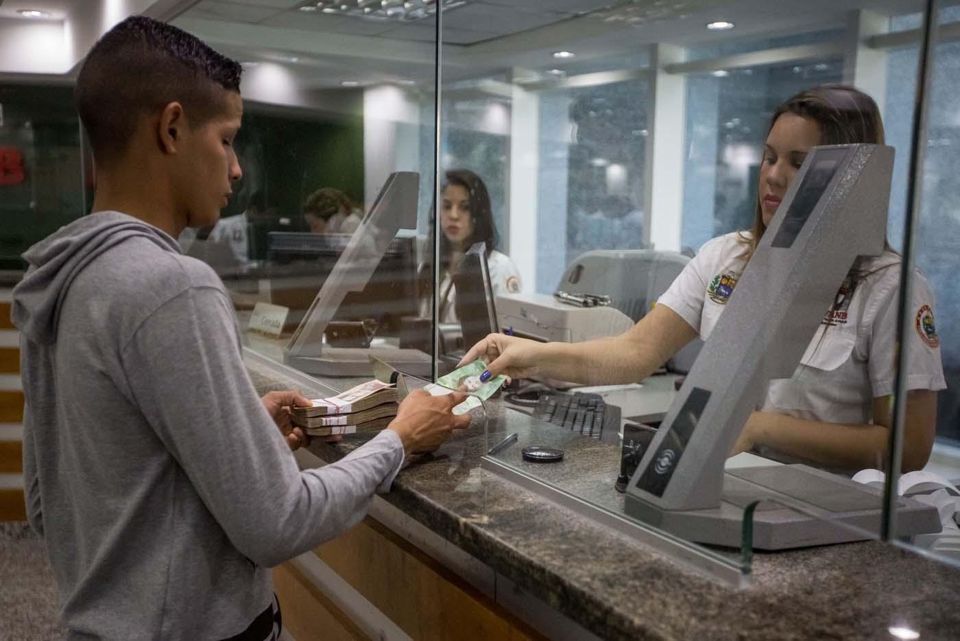 """CAR13. CARACAS (VENEZUELA), 16/01/2017.- Trabajadores de un banco manipulan billetes del nuevo cono monetario hoy 16 de enero de 2017, en Caracas (Venezuela). Los billetes de 500, 5.000 y 20.000 bolívares, tres de las seis piezas que conforman el nuevo cono monetario, comenzaron a circular hoy en Venezuela tal y como lo aseguró ayer el presidente, Nicolás Maduro, y un mes más tarde de lo previsto inicialmente debido a un """"sabotaje internacional"""". EFE/Miguel Gutiérrez"""