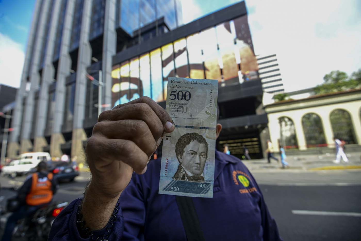 A man shows a new 500-Bolivar-note (74 cents of US dollar) in Caracas on January 16, 2017. A new family of currency will progressively come into circulation in the South American country that has the highest inflation rate in the world, which IMF forecasts say could soon hit 475 percent. / AFP PHOTO / JUAN BARRETO