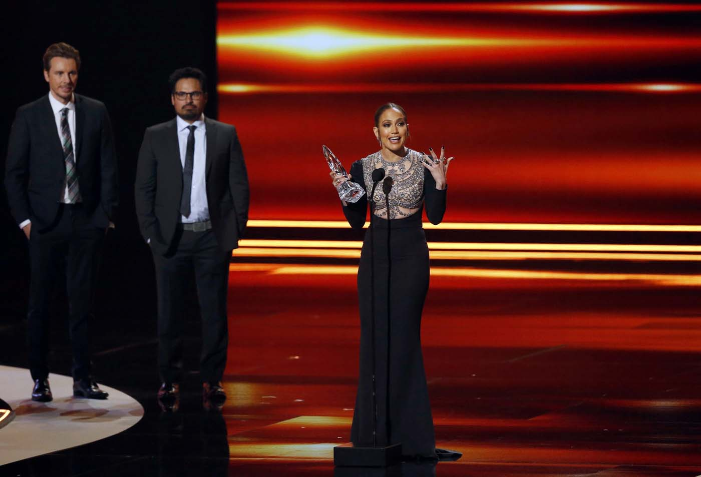 Actress Jennifer Lopez accepts the award for Favorite TV Crime Drama Actress as actors Dax Shepard (L) and Michael Pena look on during the People's Choice Awards 2017 in Los Angeles, California, U.S., January 18, 2017.   REUTERS/Mario Anzuoni