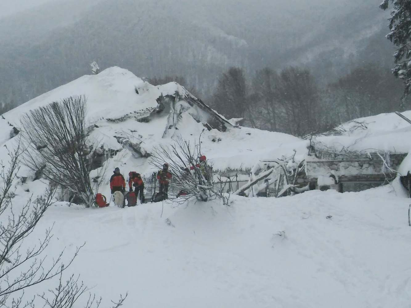 Members of Lazio's Alpine and Speleological Rescue Team stand in front of the Hotel Rigopiano in Farindola, central Italy, hit by an avalanche, in this January 19, 2017 handout picture provided by Lazio's Alpine and Speleological Rescue Team. Soccorso Alpino Speleologico Lazio/Handout via REUTERS ATTENTION EDITORS - THIS IMAGE WAS PROVIDED BY A THIRD PARTY. EDITORIAL USE ONLY. NO RESALES. NO ARCHIVE.