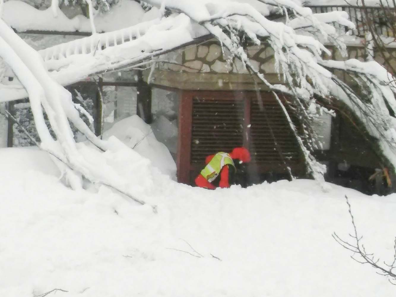 A member of Lazio's Alpine and Speleological Rescue Team is seen in front of the Hotel Rigopiano in Farindola, central Italy, hit by an avalanche, in this January 19, 2017 handout picture provided by Lazio's Alpine and Speleological Rescue Team. Soccorso Alpino Speleologico Lazio/Handout via REUTERS ATTENTION EDITORS - THIS IMAGE WAS PROVIDED BY A THIRD PARTY. EDITORIAL USE ONLY. NO RESALES. NO ARCHIVE.