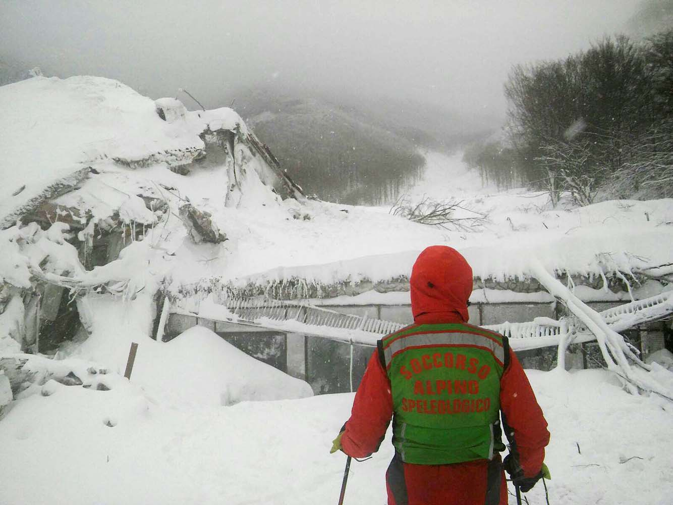 A member of Lazio's Alpine and Speleological Rescue Team stands in front of the Hotel Rigopiano in Farindola, central Italy, hit by an avalanche, in this January 19, 2017 handout picture provided by Lazio's Alpine and Speleological Rescue Team. Soccorso Alpino Speleologico Lazio/Handout via REUTERS ATTENTION EDITORS - THIS IMAGE WAS PROVIDED BY A THIRD PARTY. IT WAS PROCESSED BY REUTERS TO ENHANCE QUALITY. AN UNPROCESSED VERSION HAS BEEN PROVIDED SEPARATELY. EDITORIAL USE ONLY. NO RESALES. NO ARCHIVE. TPX IMAGES OF THE DAY