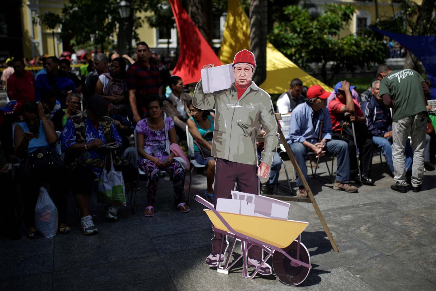 A cardboard cut-out of Venezuela's late President Hugo Chavez is seen as people wait to apply for a card that will register them for government social programmes, in Caracas, Venezuela January 20, 2017. REUTERS/Marco Bello