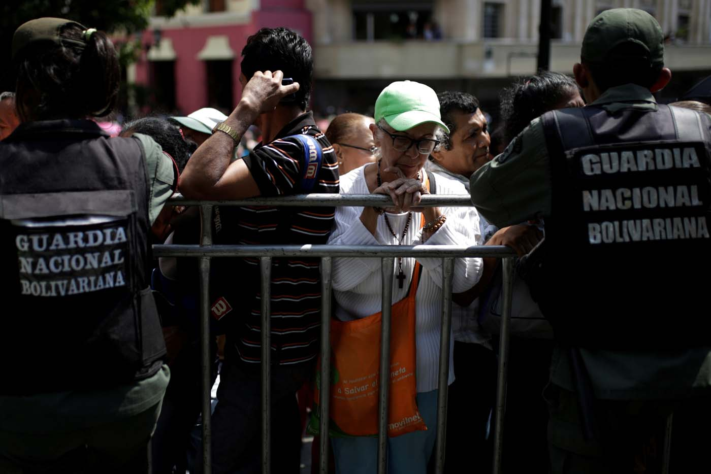 A woman waits to apply for a card that will register them for government social programmes, in front of Venezuelan National Guards, in Caracas, Venezuela January 20, 2017. REUTERS/Marco Bello
