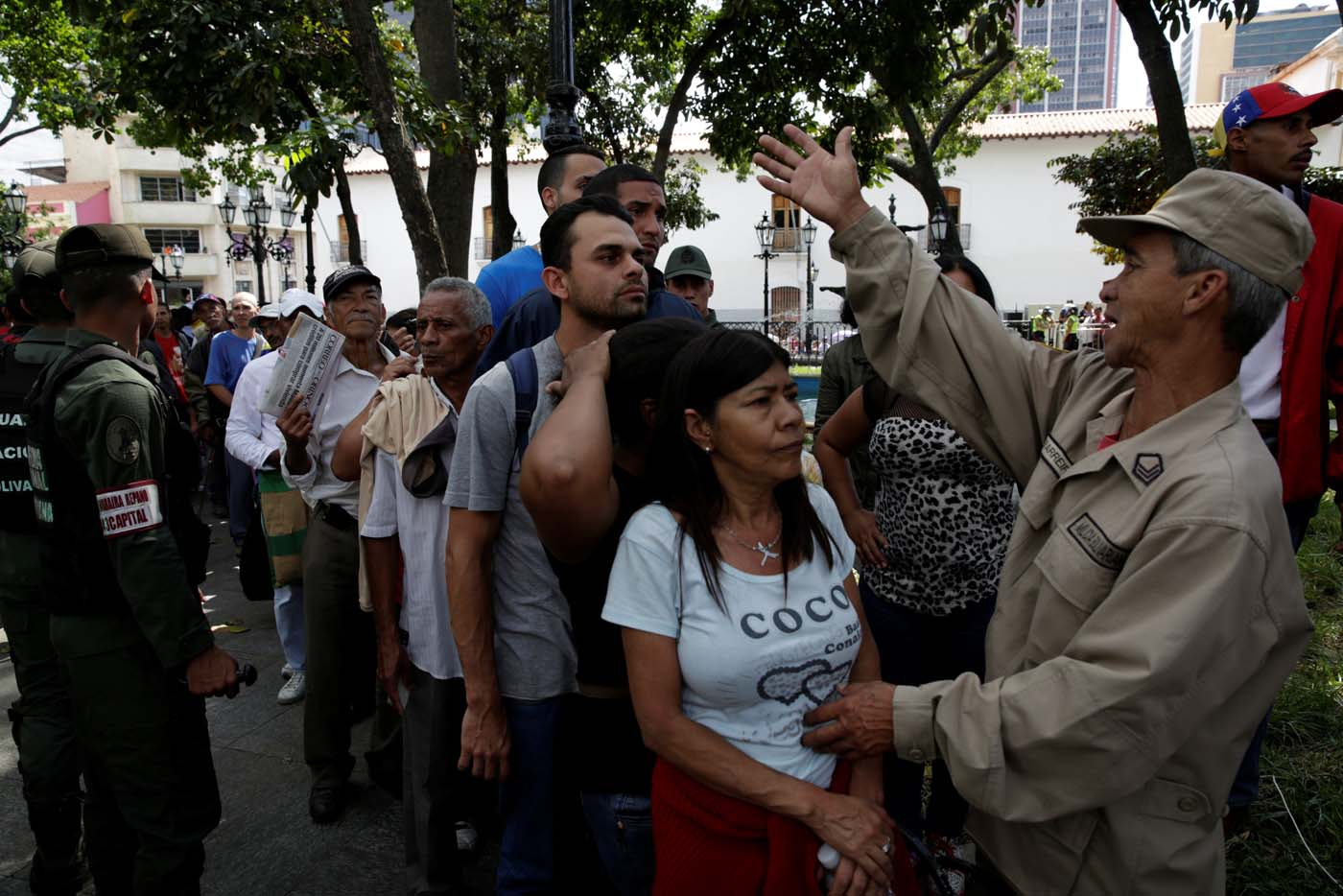 A militia member controls the crowd as people wait to apply for a card that will register them for government social programmes, in Caracas, Venezuela January 20, 2017. REUTERS/Marco Bello