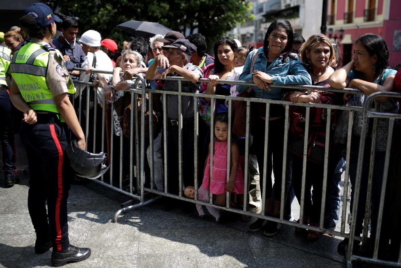 People wait to apply for a card that will register them for government social programmes, in front of a police officer, in Caracas, Venezuela January 20, 2017. REUTERS/Marco Bello
