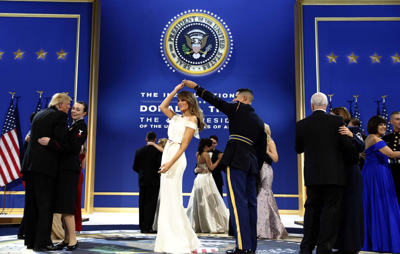 President Donald Trump, left, dances with Navy Petty Officer 2nd Class Catherine Cartmell as first lady Melania Trump is spun by Army Staff Sgt. Jose A. Medina during a dance at The Salute To Our Armed Services Inaugural Ball in Washington, Friday, Jan. 20, 2017. (AP Photo/Alex Brandon)