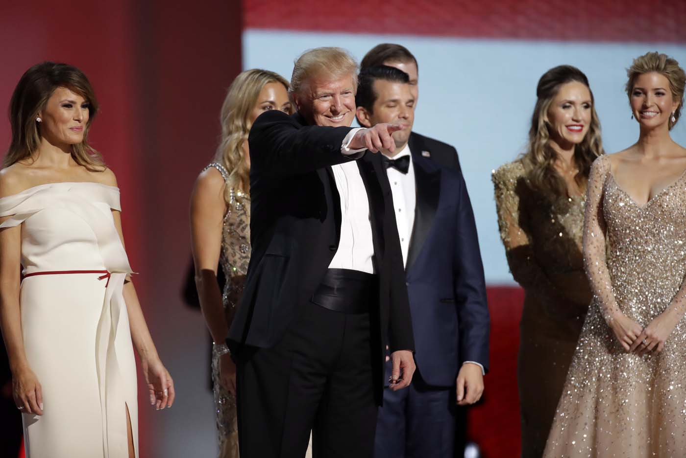 President Donald Trump, center, acknowledges supporters after dancing with first lady Melania Trump, left, and family at the Liberty Ball, Friday, Jan. 20, 2017, in Washington. (AP Photo/Patrick Semansky)