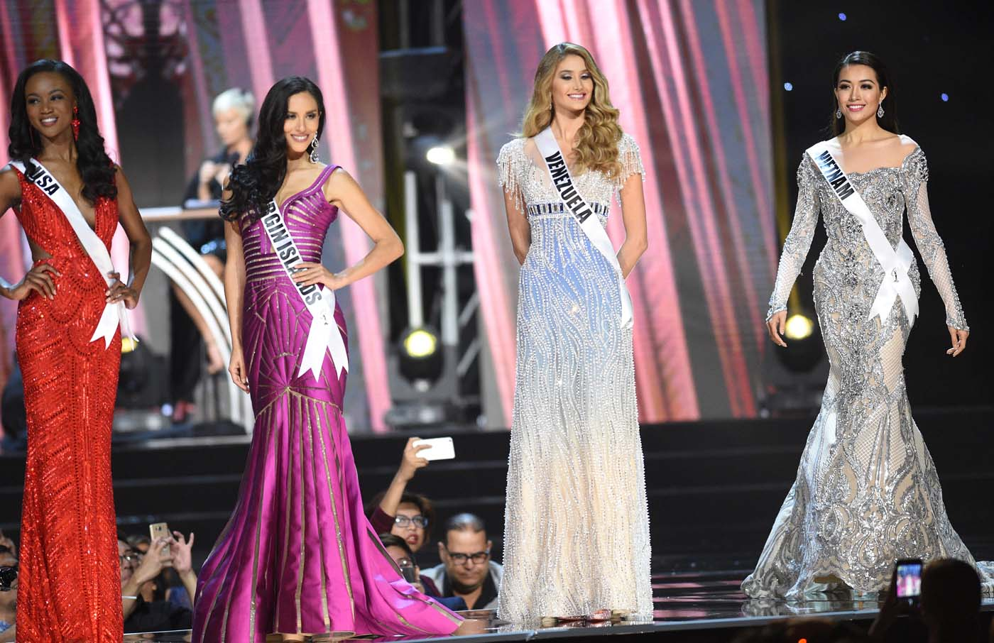 This photo taken on January 26, 2017 shows Miss Universe contestant Le Hang (R) of Vietnam in her long gown along with other candidates during the preliminary competition of the Miss Universe pageant at the Mall of Asia arena in Manila. / AFP PHOTO / TED ALJIBE