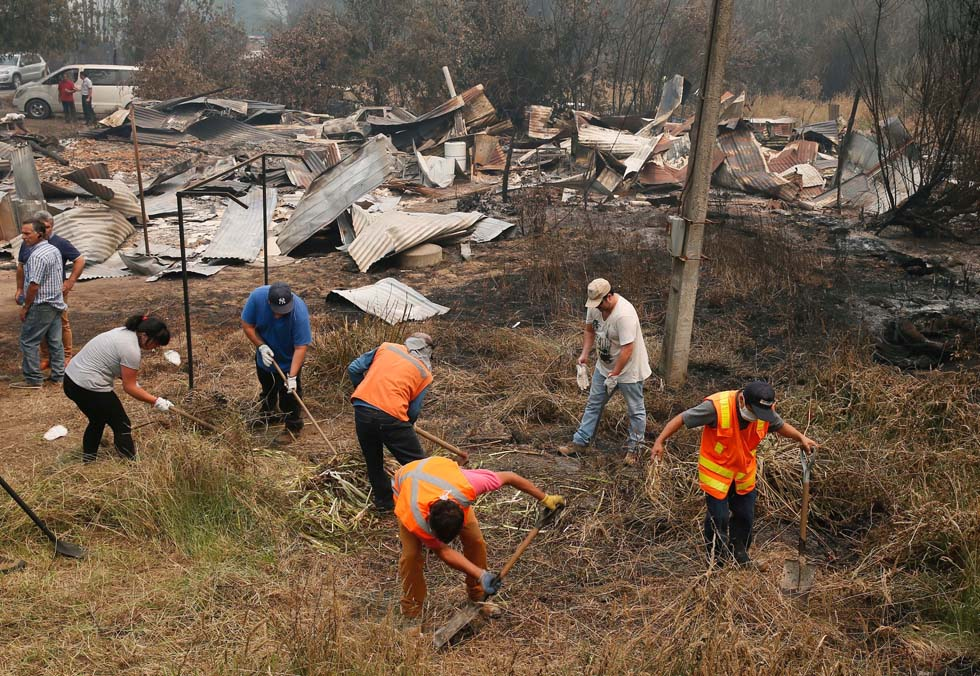 Residents clear the vegetation next to remains of a burned down public school, while wildfires ravaged wide swaths of the country's central-south regions, in town of Hualqui