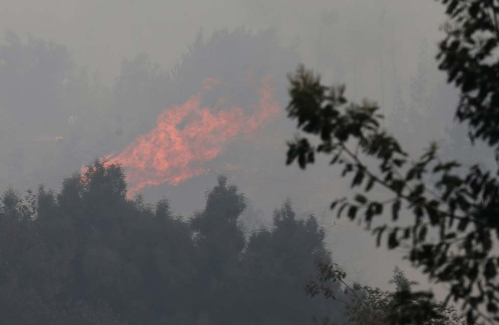 A forest fire on a hill is seen as wildfires ravage wide swaths of the country's central-south regions, in the town of Hualqui