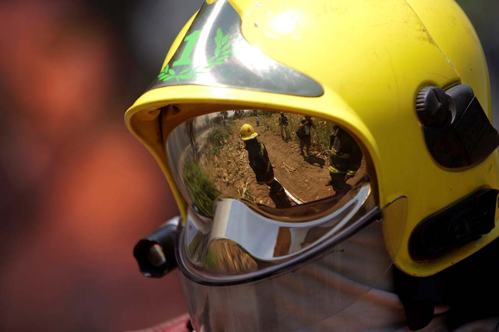 A firefighter wears a helmet as they arrive to extinguish wildfires in the country's central-south regions, in San Carlos,
