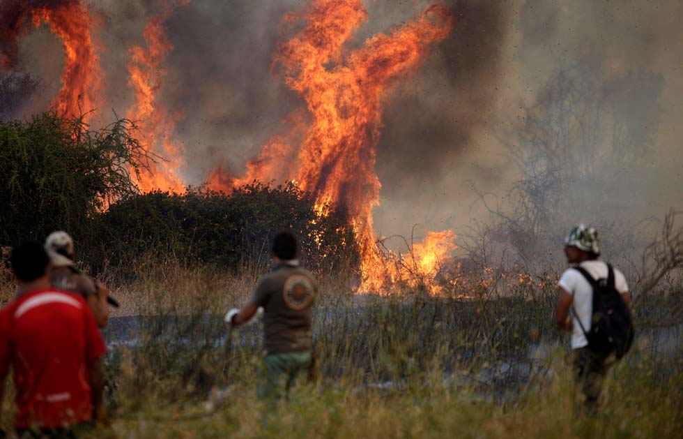 People are pictured during a forest fire in San Carlos town, at the country's central-south regions,