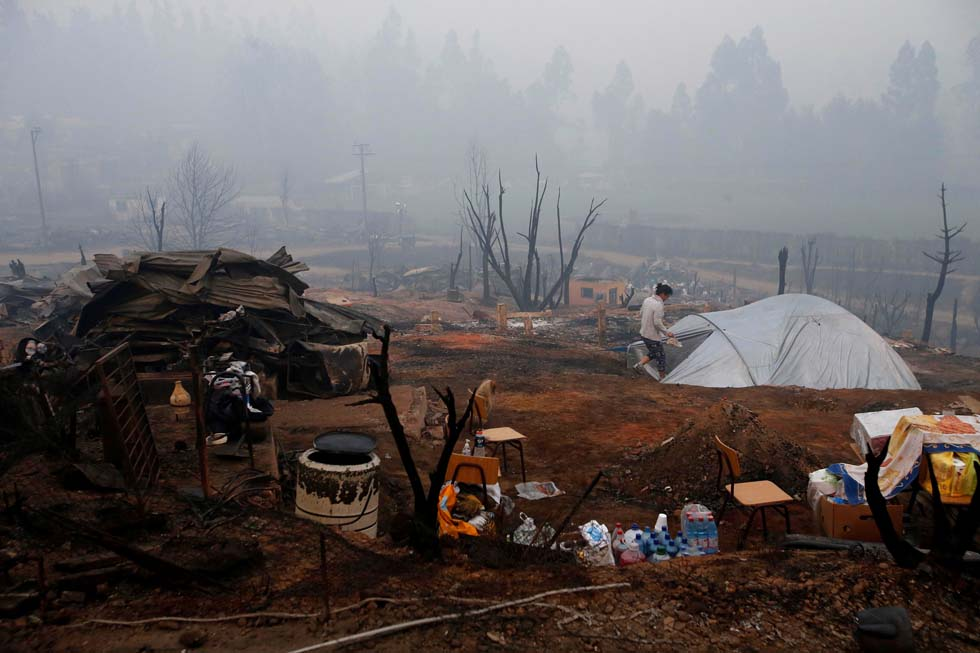 A tent is pictured among the remains of burned houses after a wildfire at the country's central-south regions in Santa Olga