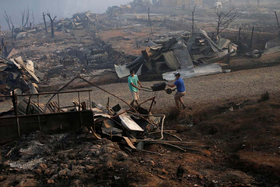 People carry a wheelbarrow among the remains of burnt houses after a wildfire at the country's central-south regions, in Santa Olga