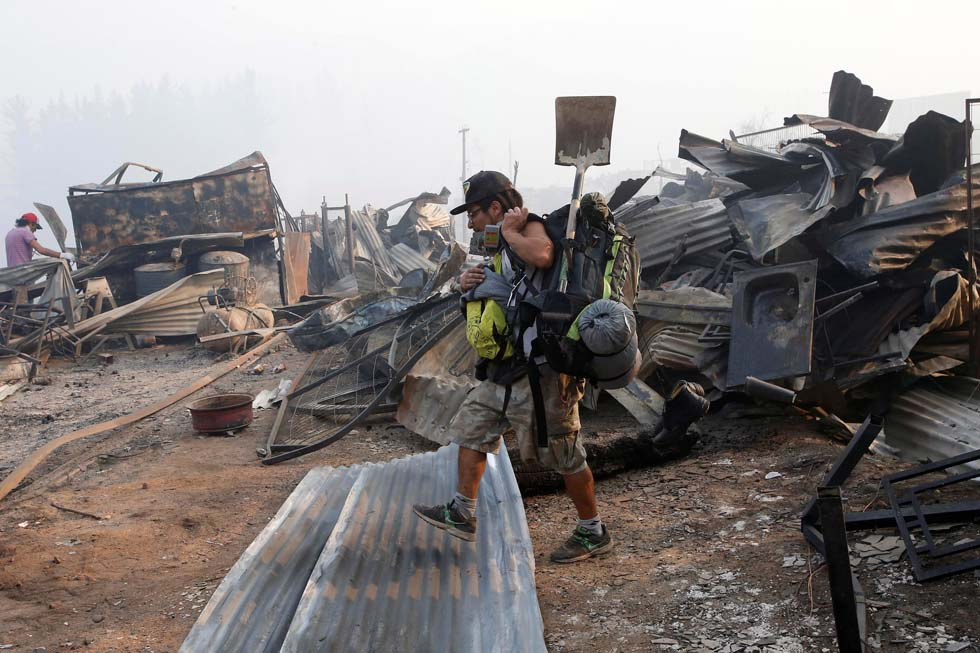 A man walks among the remains of burnt houses after a wildfire at the country's central-south regions in Santa Olga