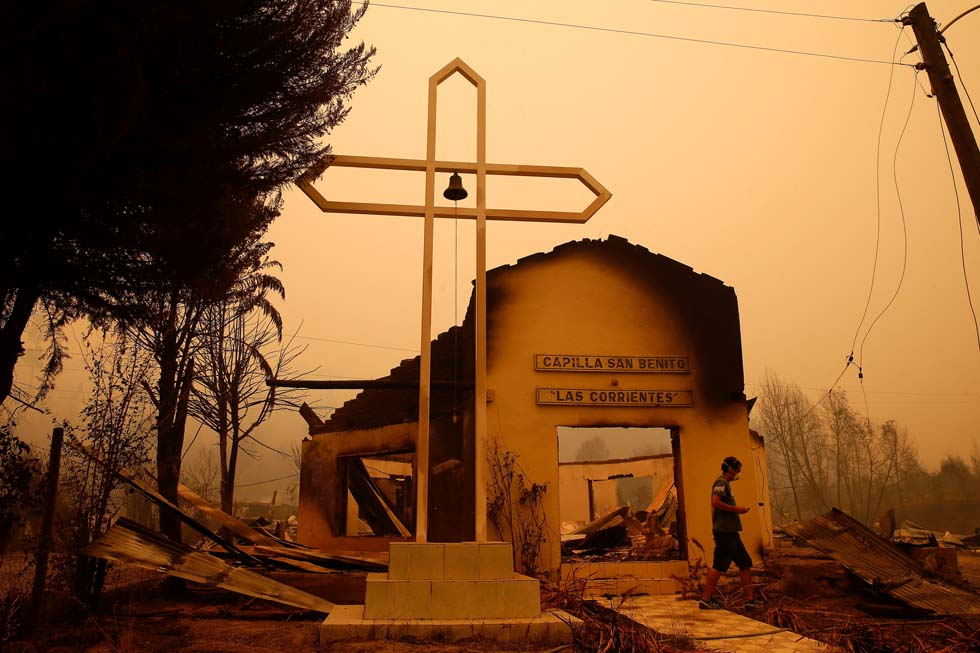 A man walks among the remains of a burnt church after a wildfire at the country's central-south regions in Santa Olga, Chile