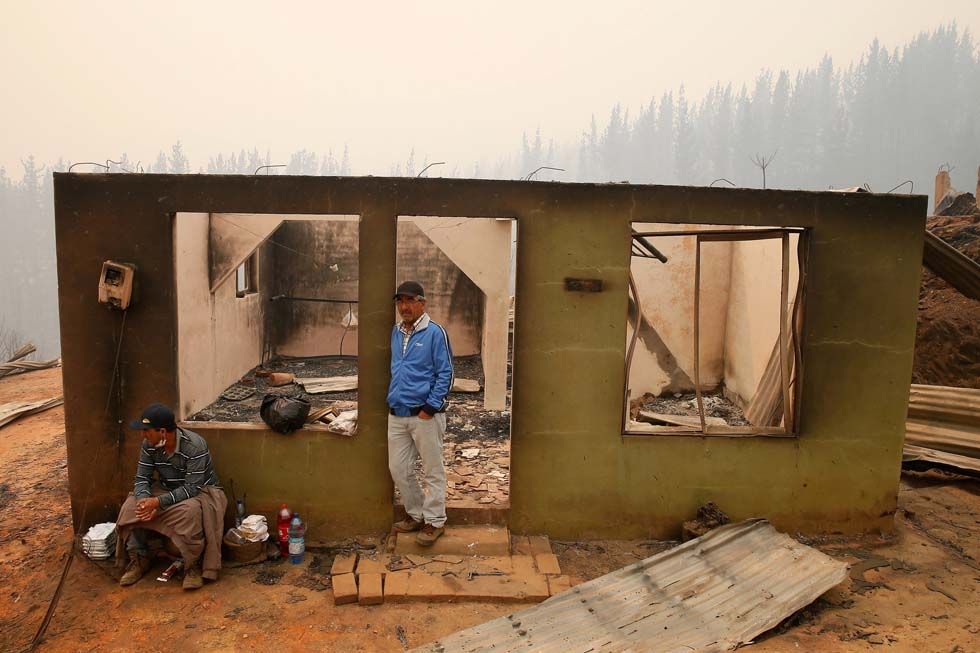 People stay at the remains of a burnt house after a wildfire at the country's central-south regions, in Santa Olga,