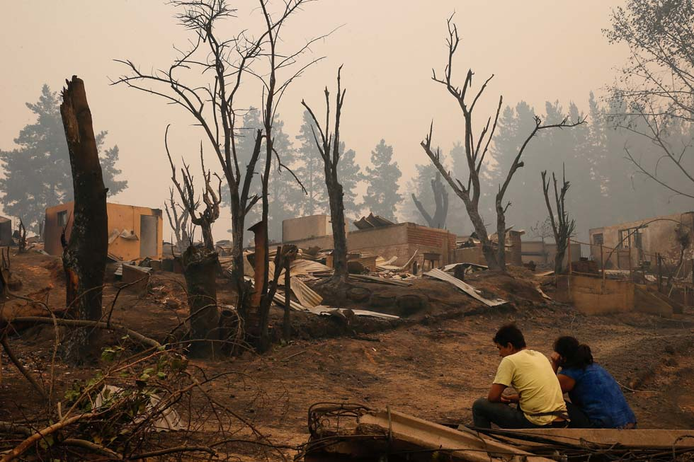 People sit near burnt houses after a wildfire in the country's central-south regions, in Santa Olga