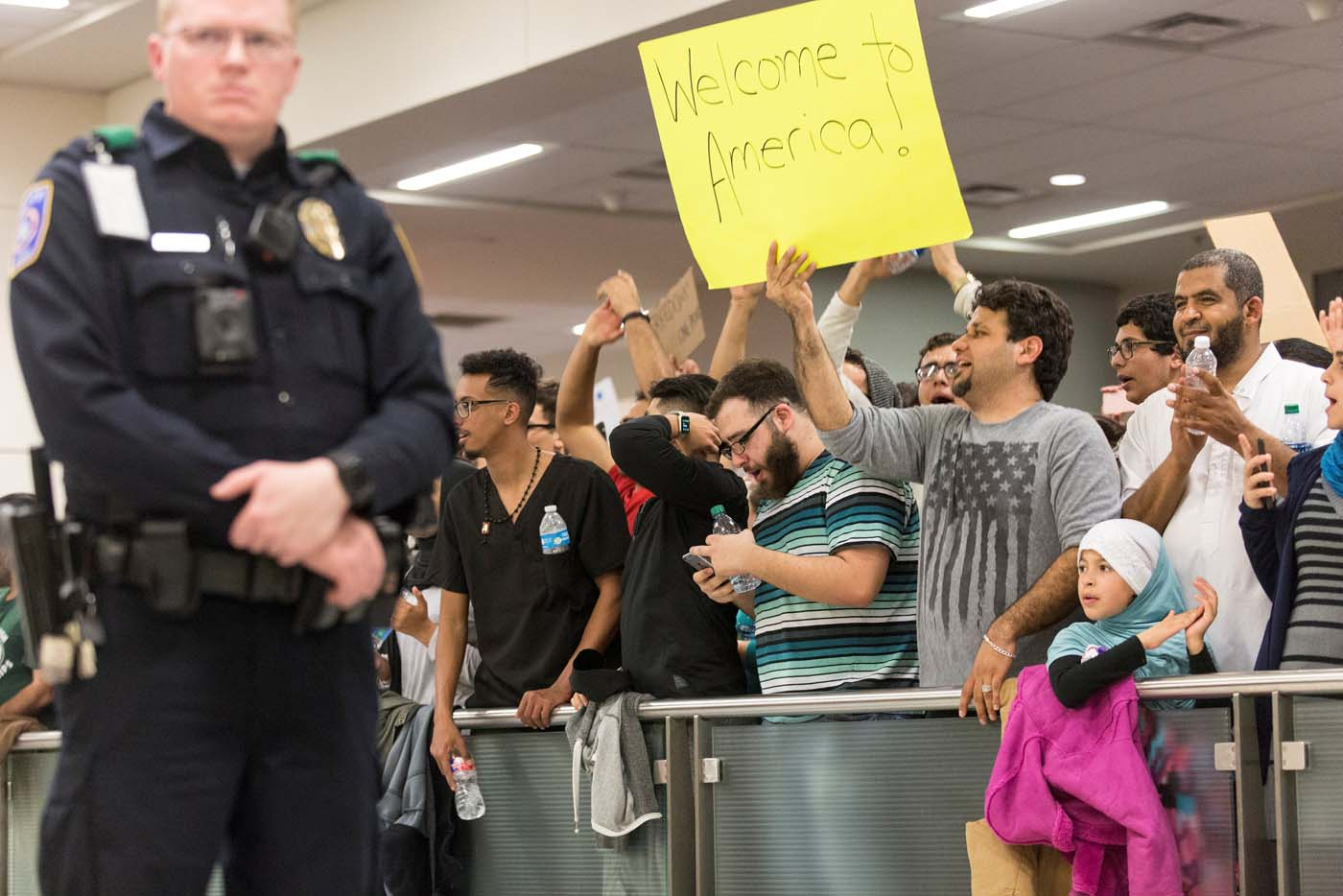 A man holds a sign as people protest against the travel ban imposed by U.S. President Donald Trump's executive order, at Dallas/Fort Worth International Airport in Dallas, Texas, U.S. January 28, 2017. REUTERS/Laura Buckman