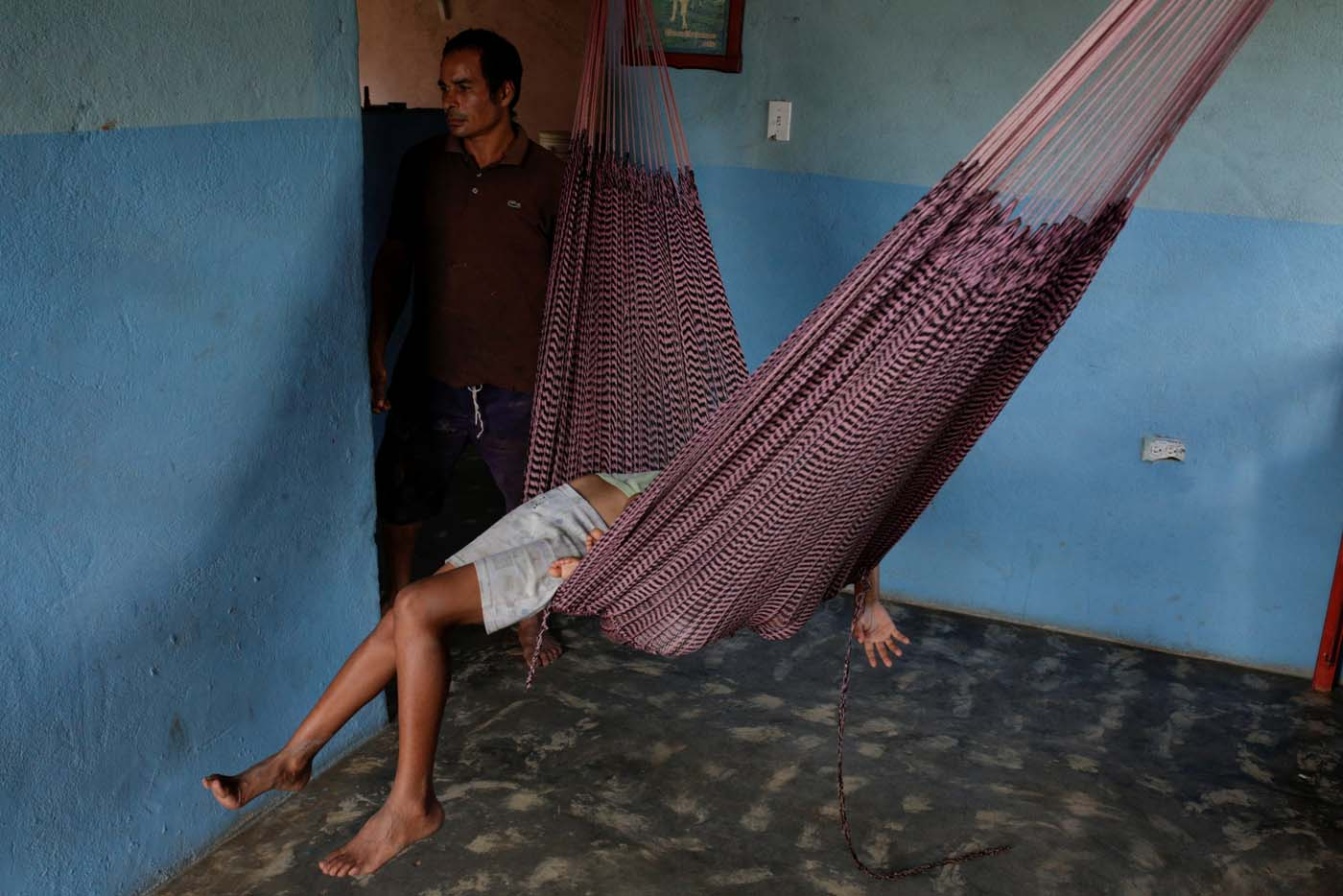 Tulio Medina, father of Eliannys Vivas, who died from diphtheria, stands next to his children as they rest in a hammock at their home in Pariaguan, Venezuela January 26, 2017. Picture taken January 26, 2017. REUTERS/Marco Bello
