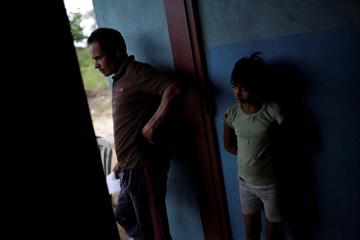 Tulio Medina (L), father of Eliannys Vivas, who died from diphtheria, stands next to one of his daughters at the entrance of their home in Pariaguan, Venezuela January 26, 2017. Picture taken January 26, 2017. REUTERS/Marco Bello