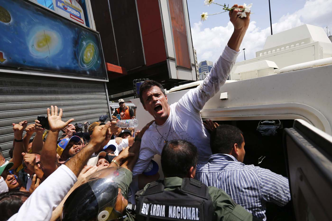 Venezuelan opposition leader Leopoldo Lopez gets into a National Guard armored vehicle in Caracas February 18, 2014. Lopez, wanted on charges of fomenting deadly violence, handed himself over to security forces on Tuesday, Reuters witnesses said. Lopez, a 42-year-old U.S.-educated economist who has spearheaded a recent wave of protests in Venezuela, got into an armored vehicle after giving a speech to an opposition rally in Caracas. REUTERS/Jorge Silva (VENEZUELA - Tags: POLITICS CIVIL UNREST)