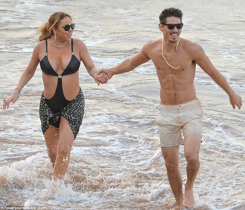 Mariah Carey in swimsuit holding hands with Bryan Tanaka on the beach