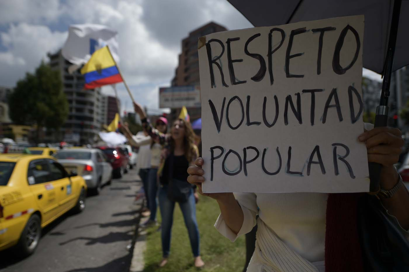 """Supporters of Ecuadorean presidential candidate for the CREO party Guillermo Lasso, protest with a sign reading """"Respect popular will"""" outside the National Electoral Council in Quito on February 20, 2017, as they wait for the final results of Sunday's presidential election. Leftist Lenin Moreno was crossing his fingers Monday for outright victory in Ecuador's presidential vote, but risked being forced into a runoff that could shift the country to the right. With nearly 89 percent of the votes counted, he was still short with 39.10 percent, against 28.3 percent for his conservative competitor, Guillermo Lasso. / AFP PHOTO / RODRIGO BUENDIA"""
