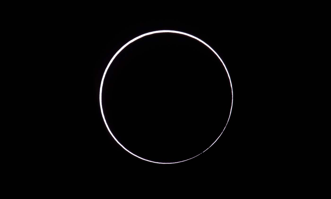 """Picture taken on February 26, 2017 showing an annular solar eclipse, as seen from the Estancia El Muster, near Sarmiento, Chubut province, 1600 km south of Buenos Aires, Argentina, on February 26, 2017. Stargazers applauded as they were plunged into darkness Sunday when the moon passed in front of the sun in a spectacular """"ring of fire"""" eclipse. / AFP PHOTO / ALEJANDRO PAGNI"""