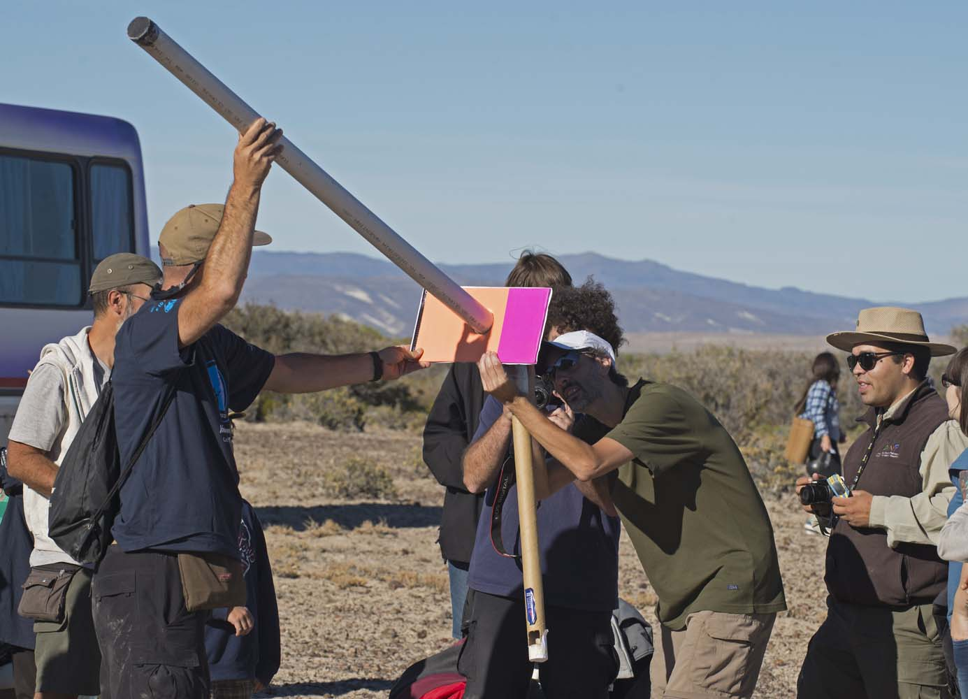 """Picture taken on February 26, 2017 showing people preparing to see an annular solar eclipse, at the Estancia El Muster, near Sarmiento, Chubut province, 1600 km south of Buenos Aires, Argentina, on February 26, 2017. Stargazers applauded as they were plunged into darkness Sunday when the moon passed in front of the sun in a spectacular """"ring of fire"""" eclipse. / AFP PHOTO / ALEJANDRO PAGNI"""