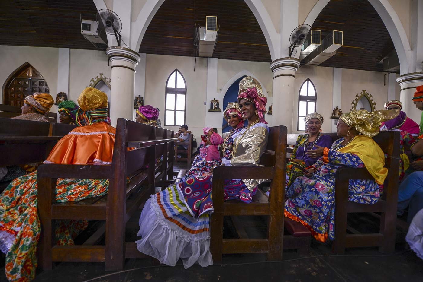 "Women dressed as ""madamas"" attend a mass before the beginning of the Carnival in El Callao, in Bolivar state, Venezuela on February 26, 2017.  El Callao's carnival was recently named Unesco's Intangible Cultural Heritage of Humanity and is led by the madamas, the pillars of Callaoense identity representing Antillean matrons considered the communicators of values, who dance and wear colourful dresses. / AFP PHOTO / JUAN BARRETO"