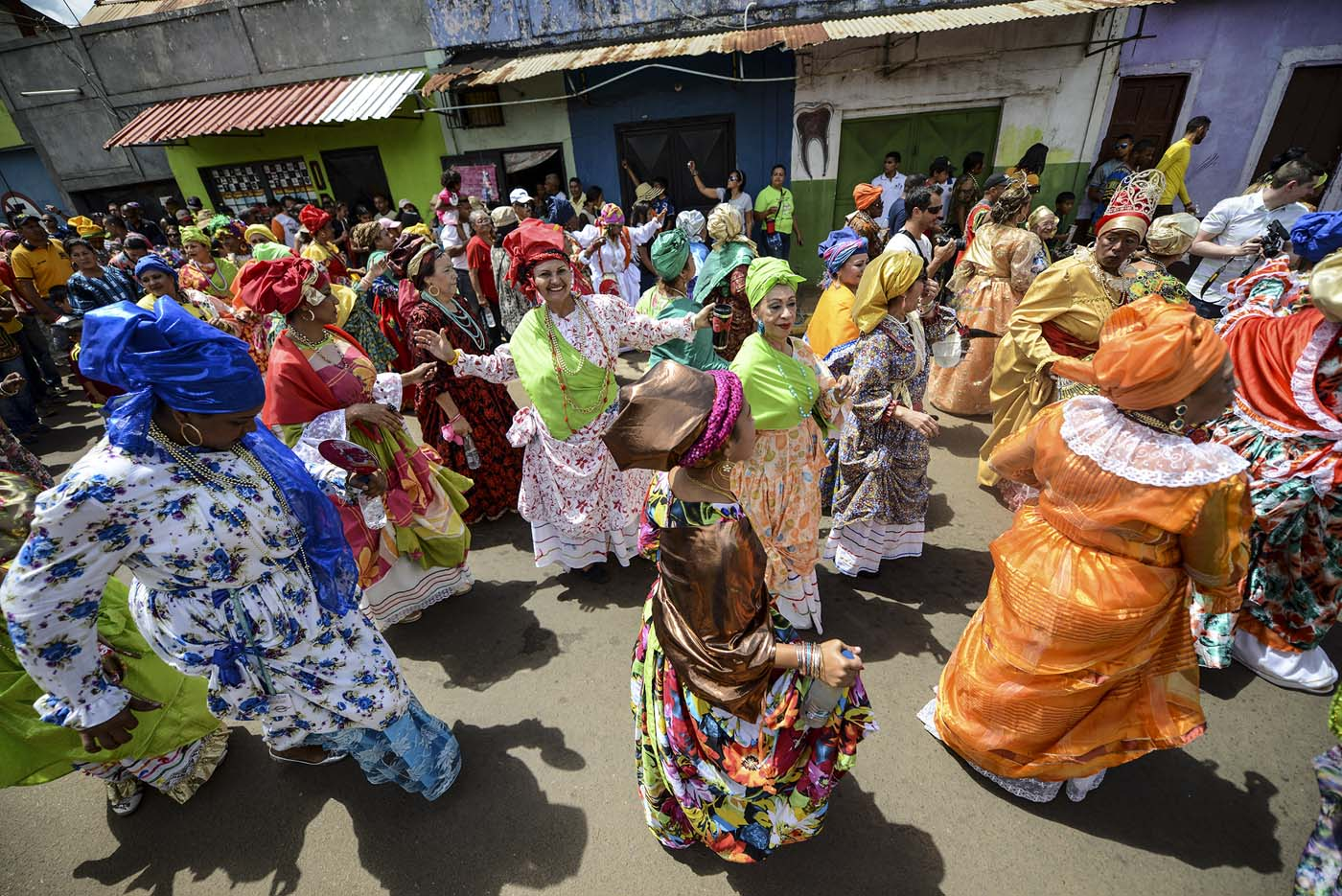 "Women dressed as ""madamas"" dance as they take part in a parade during the Carnival in El Callao, Bolivar state, Venezuela on February 26, 2017.  El Callao's carnival was recently named Unesco's Intangible Cultural Heritage of Humanity and is led by the madamas, the pillars of Callaoense identity representing Antillean matrons considered the communicators of values, who dance and wear colourful dresses. / AFP PHOTO / JUAN BARRETO"