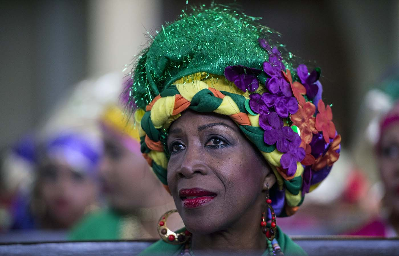 "A woman dressed as ""madama"" attend a mass before the beginning of the Carnival in El Callao, Bolivar state, Venezuela on February 26, 2017.  El Callao's carnival was recently named Unesco's Intangible Cultural Heritage of Humanity and is led by the madamas, the pillars of Callaoense identity representing Antillean matrons considered the communicators of values, who dance and wear colourful dresses. / AFP PHOTO / JUAN BARRETO"