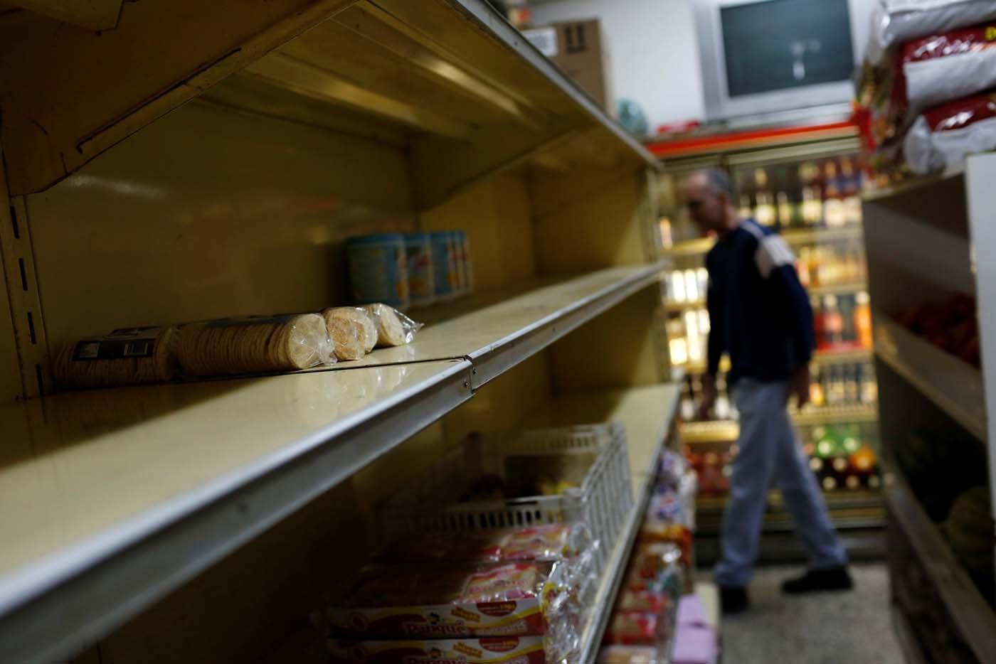 A man walks past empty shelves at a supermarket in Caracas, Venezuela March 9, 2017. REUTERS/Carlos Garcia Rawlins