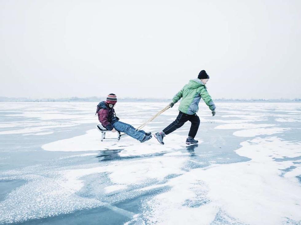 """PRIMER LUGAR, NIÑOS """"La foto fue filmada en la ciudad de Harbin, provincia de Heilongjiang en China. Dos niños jugaban con un trineo casero en el congelado río Songhua """"."""